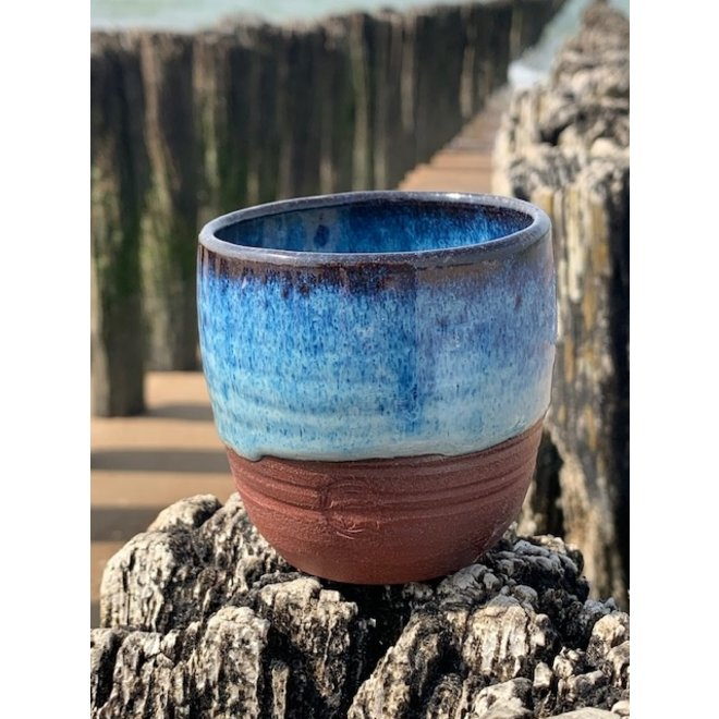 With the turntable handmade cup of Belgien red clay with a beautiful floating blue high firing glaze.