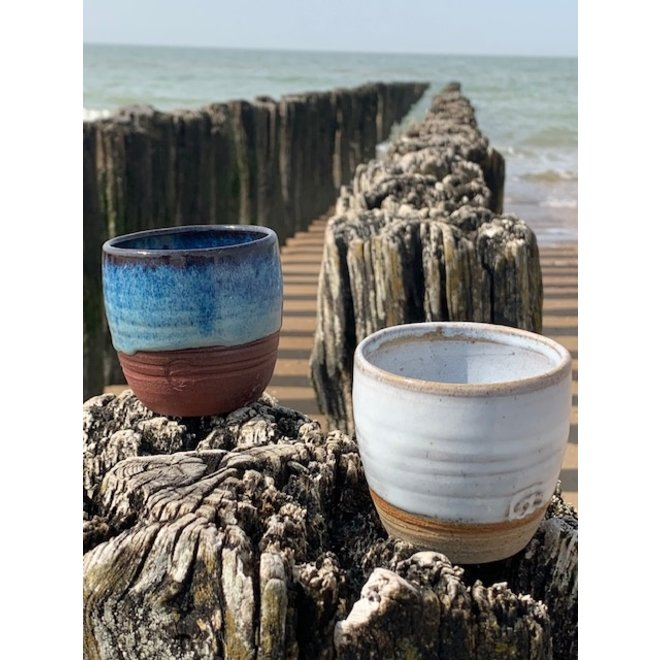 With the turntable handmade cup made with speckled Pottery clay with a beautiful opal white high firing glaze.
