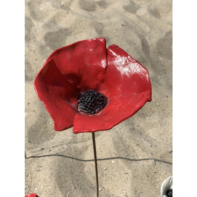The handmade poppy glazed in red with a black heart and made with a lot of passion and love. An eye catcher in the garden or planter.