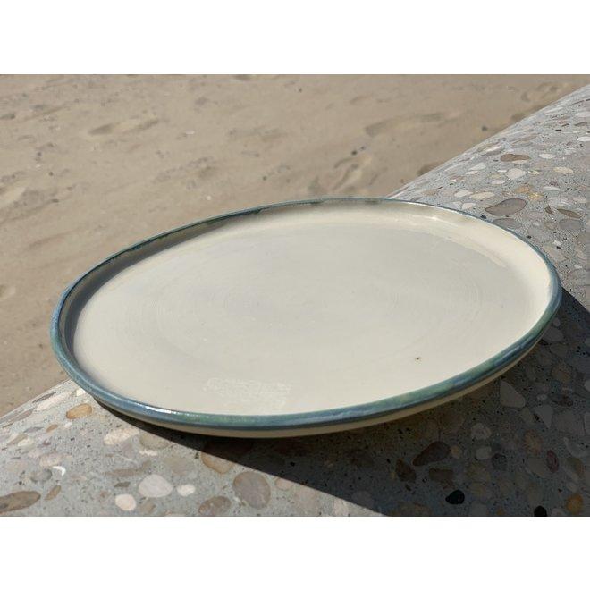 Bord handgemaakt van beige klei en afgewerkt met een groen en blauw randje