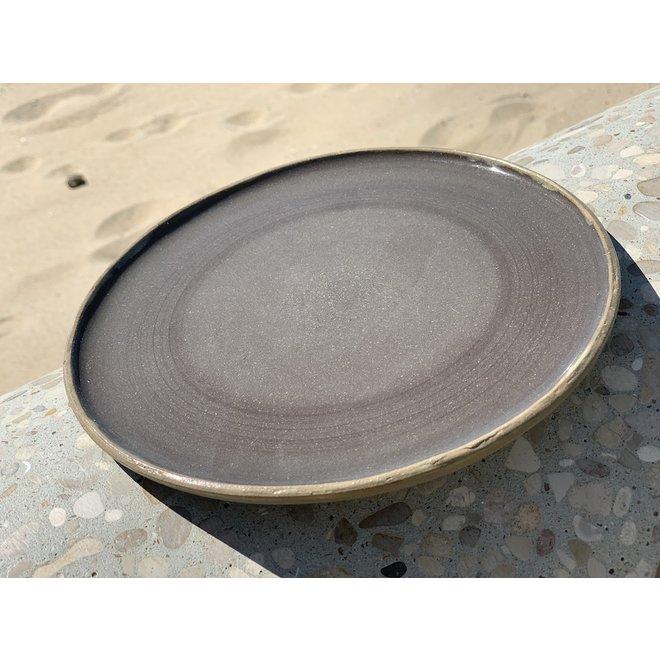 Assiette en céramique faite à la main à partir d'argile grise avec une bordure ocre peinte à la main