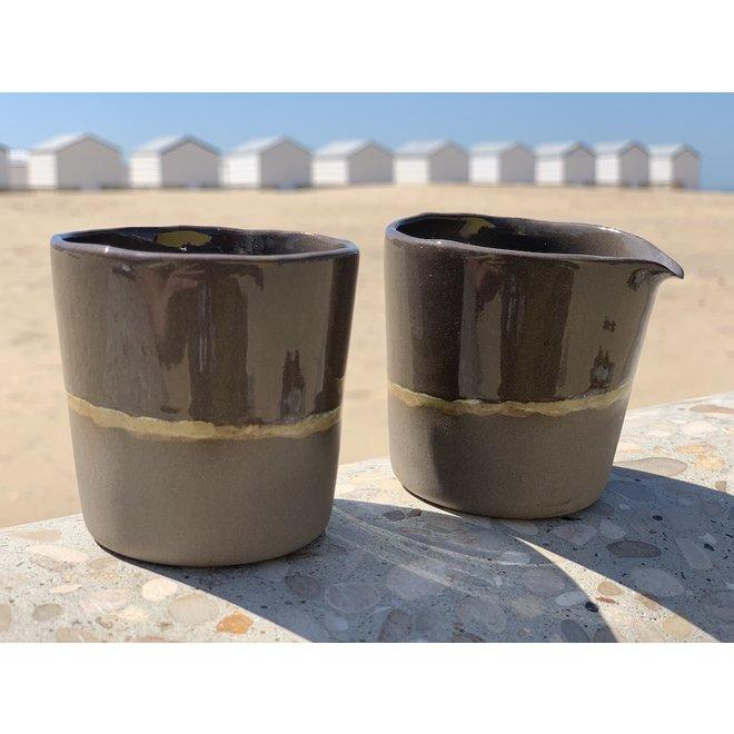 Pot à lait fait main en céramique à partir d'argile grise avec une bordure naturelle ocre