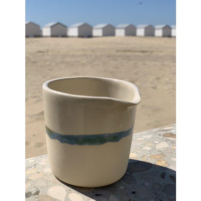 Pot à lait en céramique à la main avec une bordure subtile de vert et de bleu.