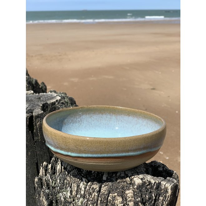 With the turntable handmade bowl of Pottery clay with a beautiful Floating light blue high-firing glaze.