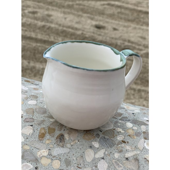 Handmade milk jug en porcelain with a green and blue edge