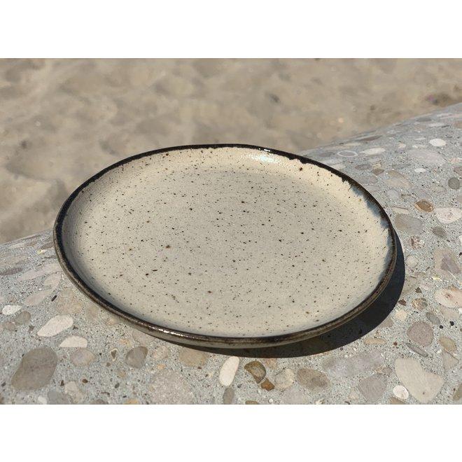 Bord handgemaakt van beige gespikkelde klei en afgewerkt met een zwart randje