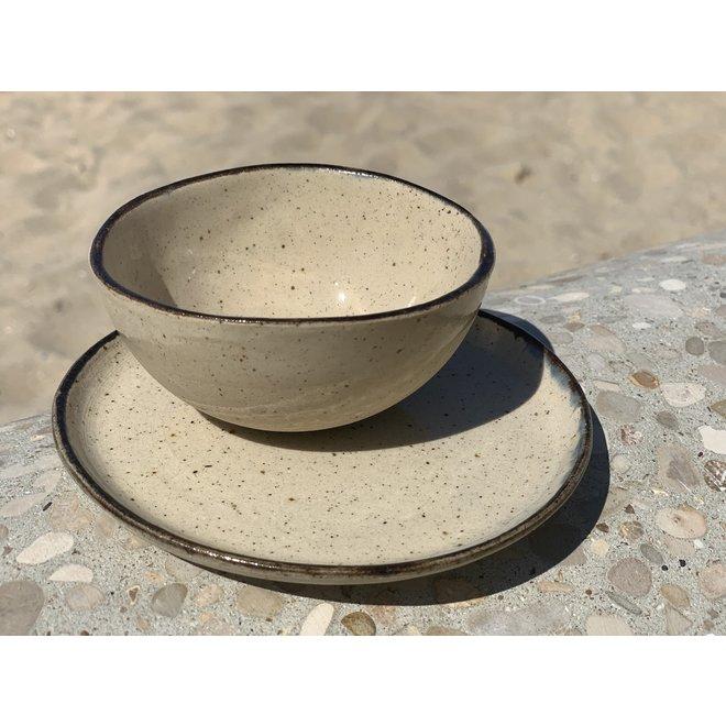 Assiette faite à la main à partir d'argile mouchetée beige et finie avec un bord noir