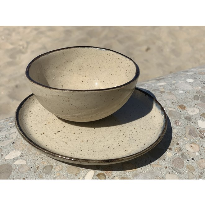 Plate handmade from beige speckled clay and finished with a black edge