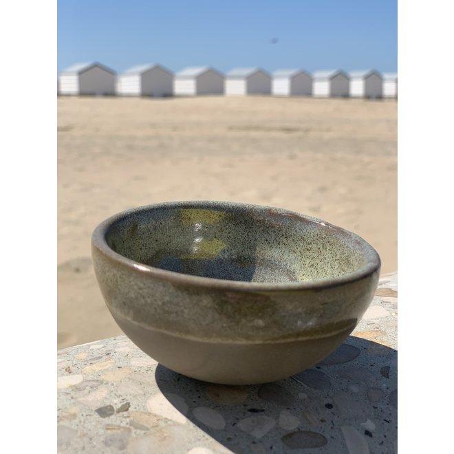 Kom in de vorm van een halve bol handgemaakt in keramiek met een groene boord