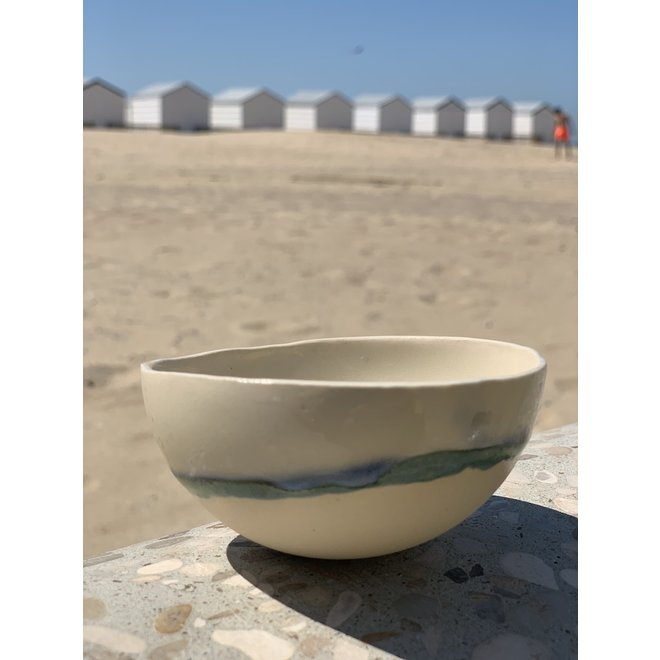 Bowl handmade in beige cast clay finished with a green, blue edge.