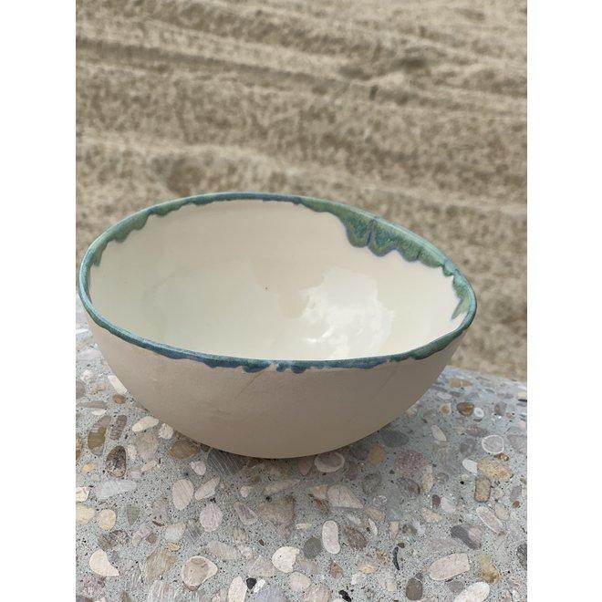 Bol fait main en terre cuite beige finie avec un bord naturel vert et bleu.