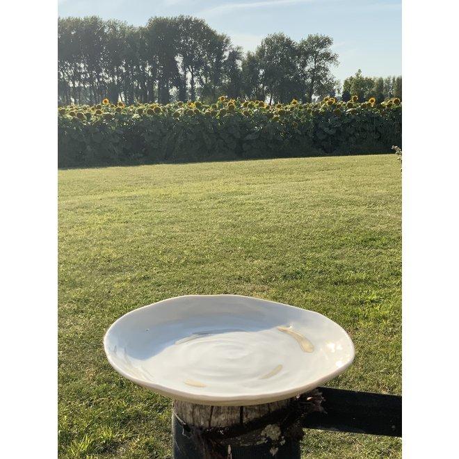 Plat ou bol fait main en porcelaine blanche avec un glaçage transparent brillant fini avec un noeud doré