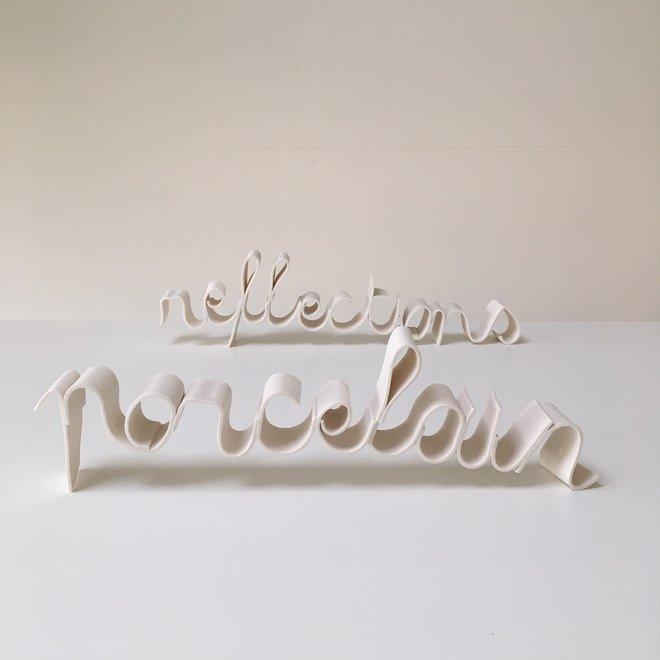 "Woorden ""Porcelain Reflections"" in porselein"