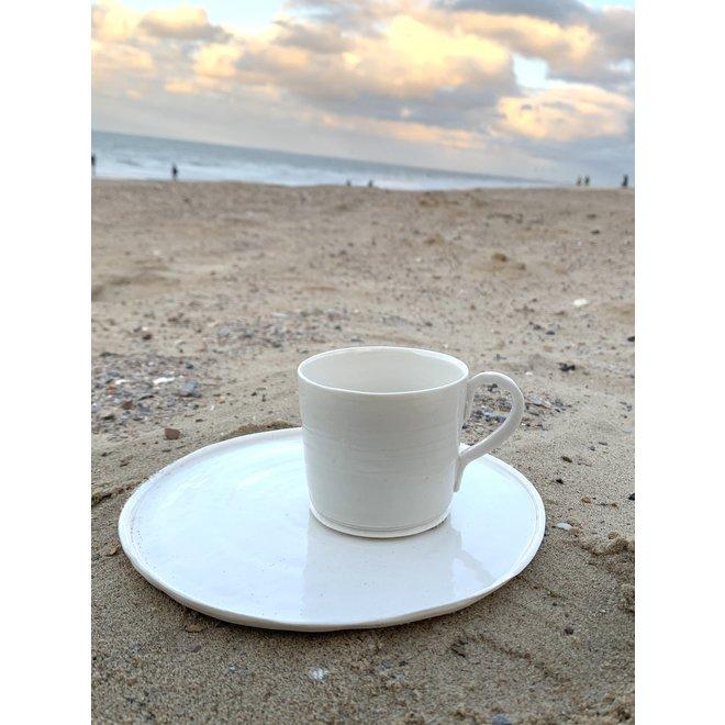 Wit porseleinen bord. Handgemaakte vorm dat straalt van klasse en siert door zijn eenvoud. Elk bordje is uniek.