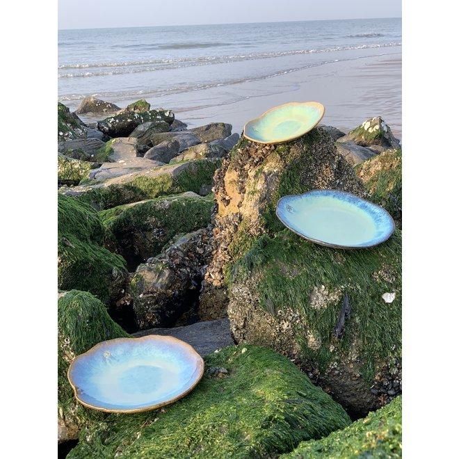 """Assiette en céramique Amandine faite à la main en forme de coquillage en émaille lagune de """"Chefs Artisann i-lign"""" pour un usage contemporain ainsi que pour la restauration."""