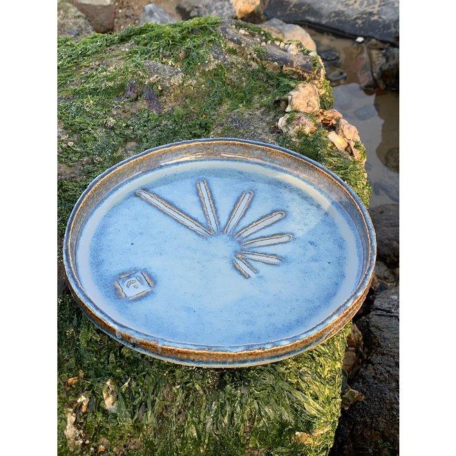 Dit handgemaakt eigentijds keramisch bord met opstaande rand heeft een ruwe presentatiebodem met streepjesstructuur en de zon als inspiratie
