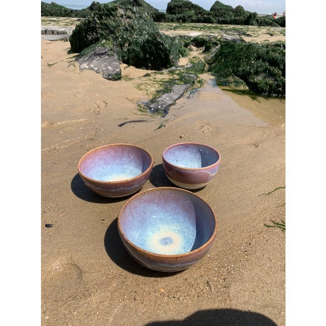 With the turntable handmade bowl of Puerite clay with a beautiful Floating magenta roos high-firing glaze.