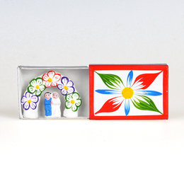 Bridal couple in matchbox, floral arch