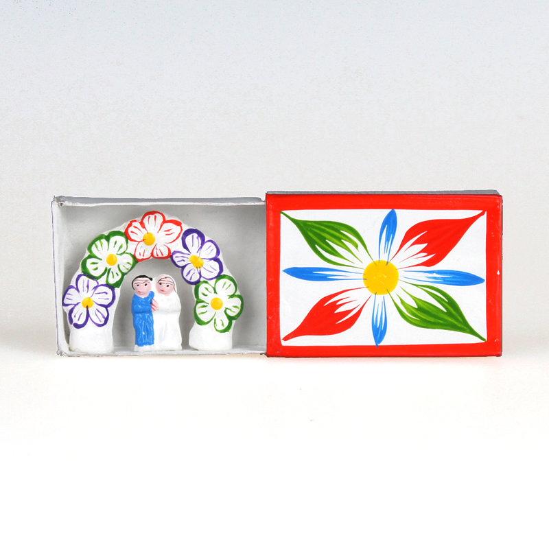 Bruidspaar in luciferdoosje, bloemenboog