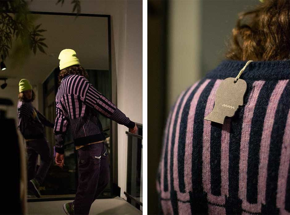staff member looks at himself in a mirror trying on a purple Brain Dead Sweater