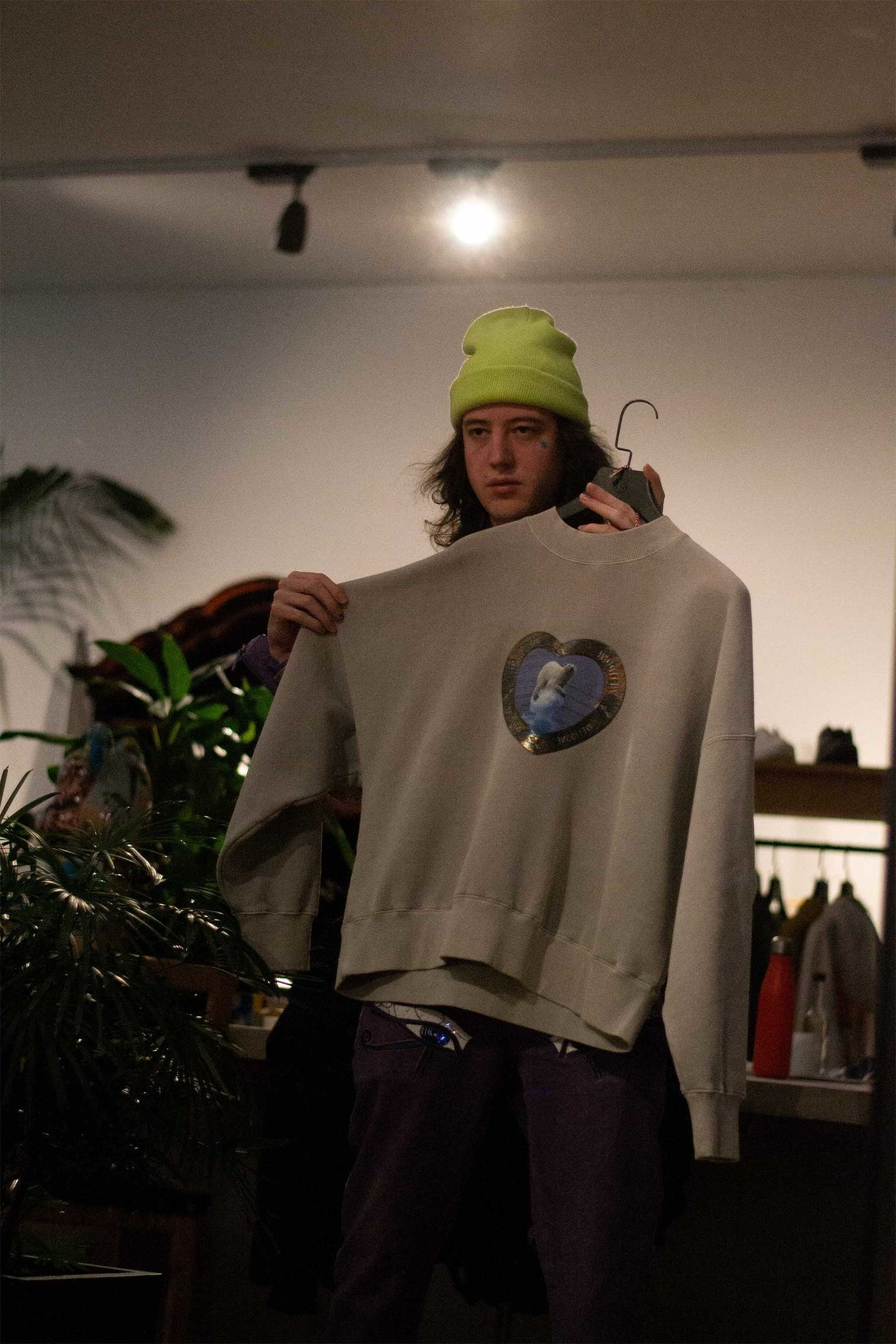 staff member holds a sweater in front of him while looking in the mirror