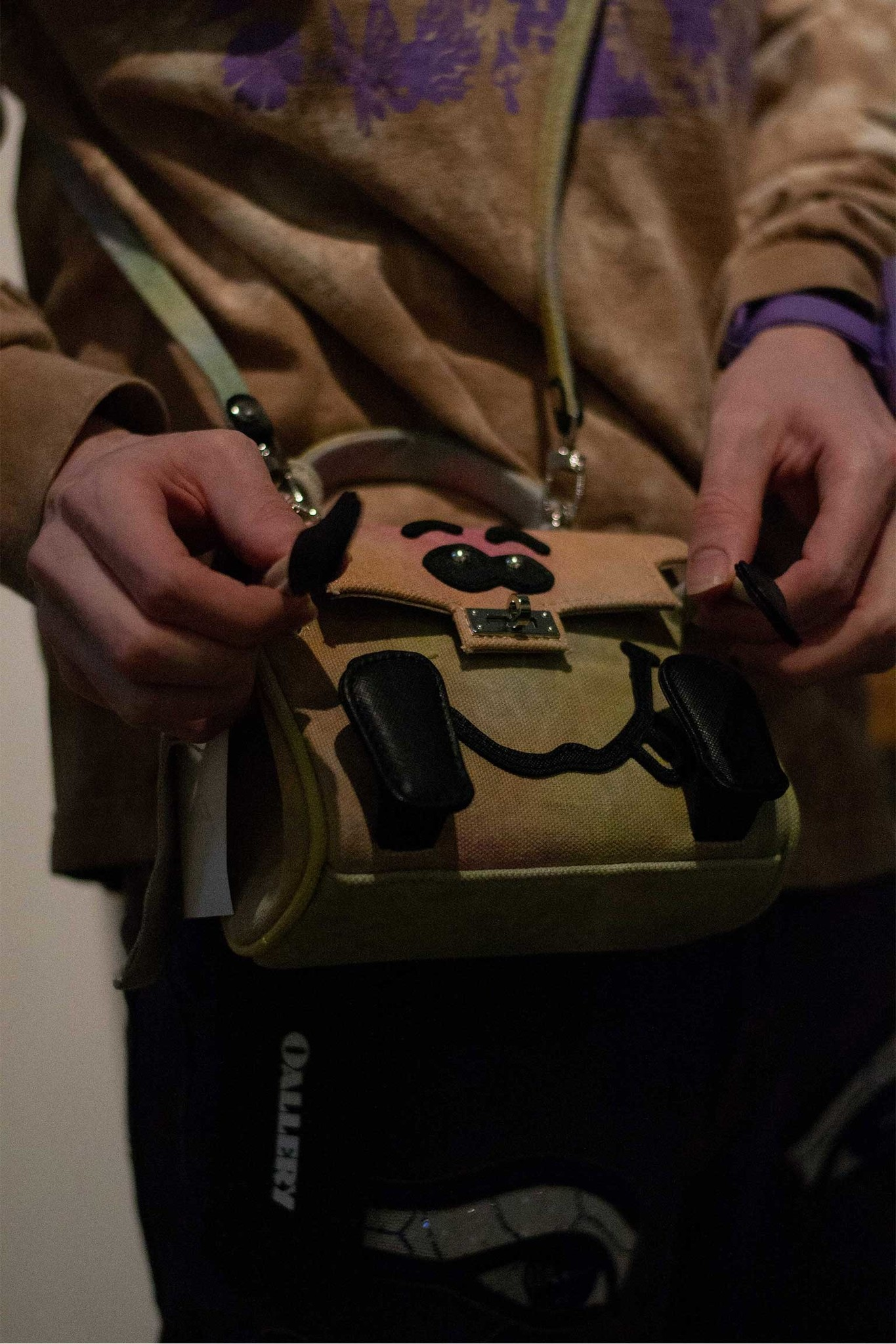 hands play with a small bag featuring leather details  forming a face