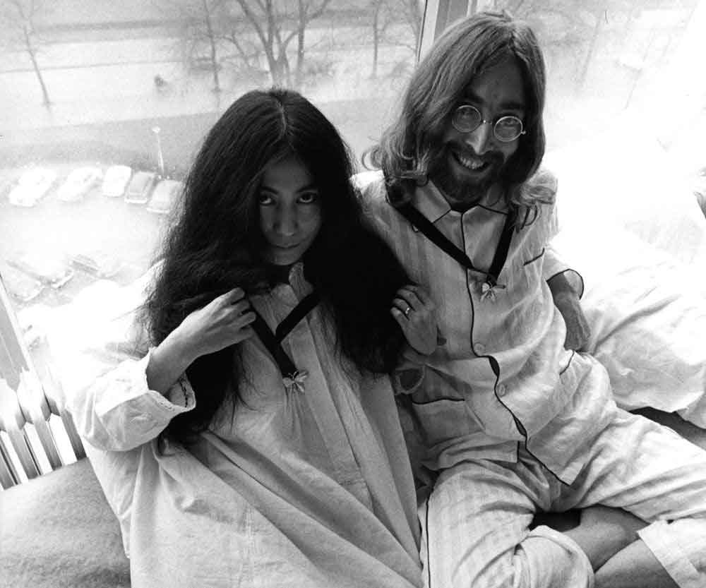John Lennon and Yoko Ono wearing pyjamas in bed at the Hilton in Amsterdam