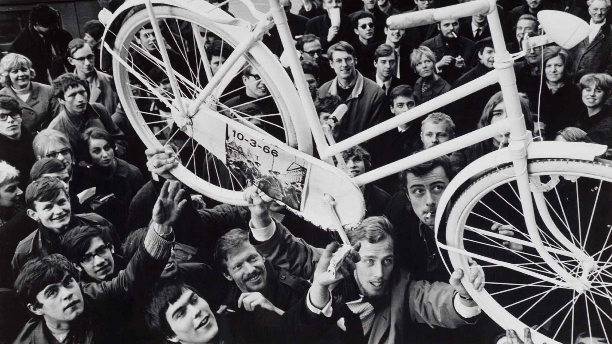 crowd hold up a bike