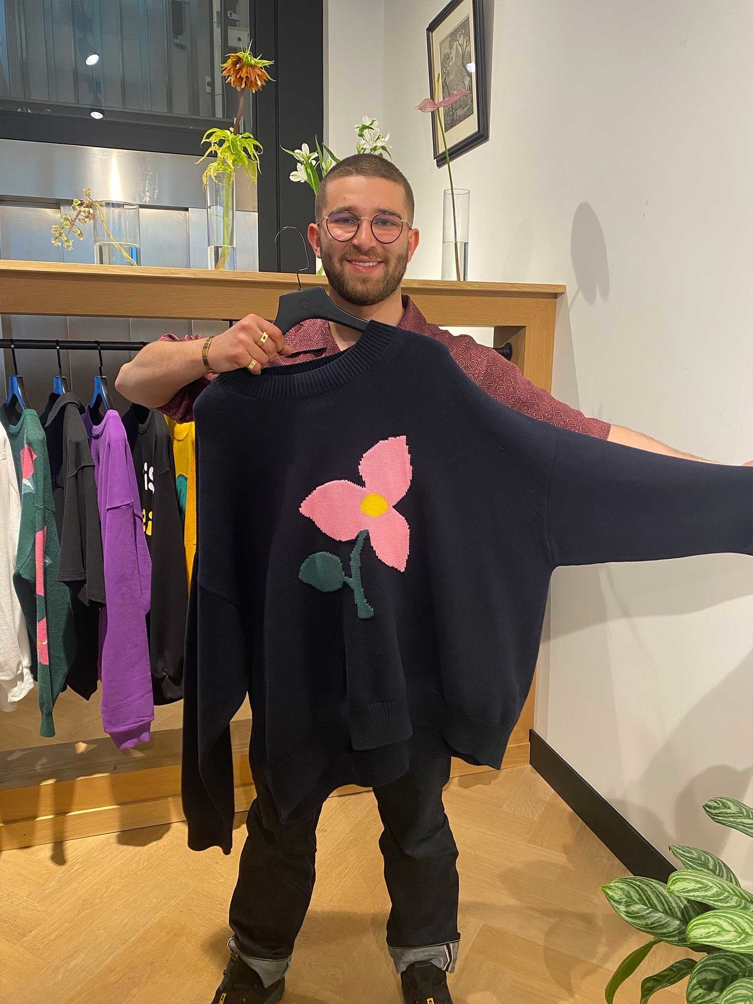 Sacha holds a FiSN sweater with a flower in the middle