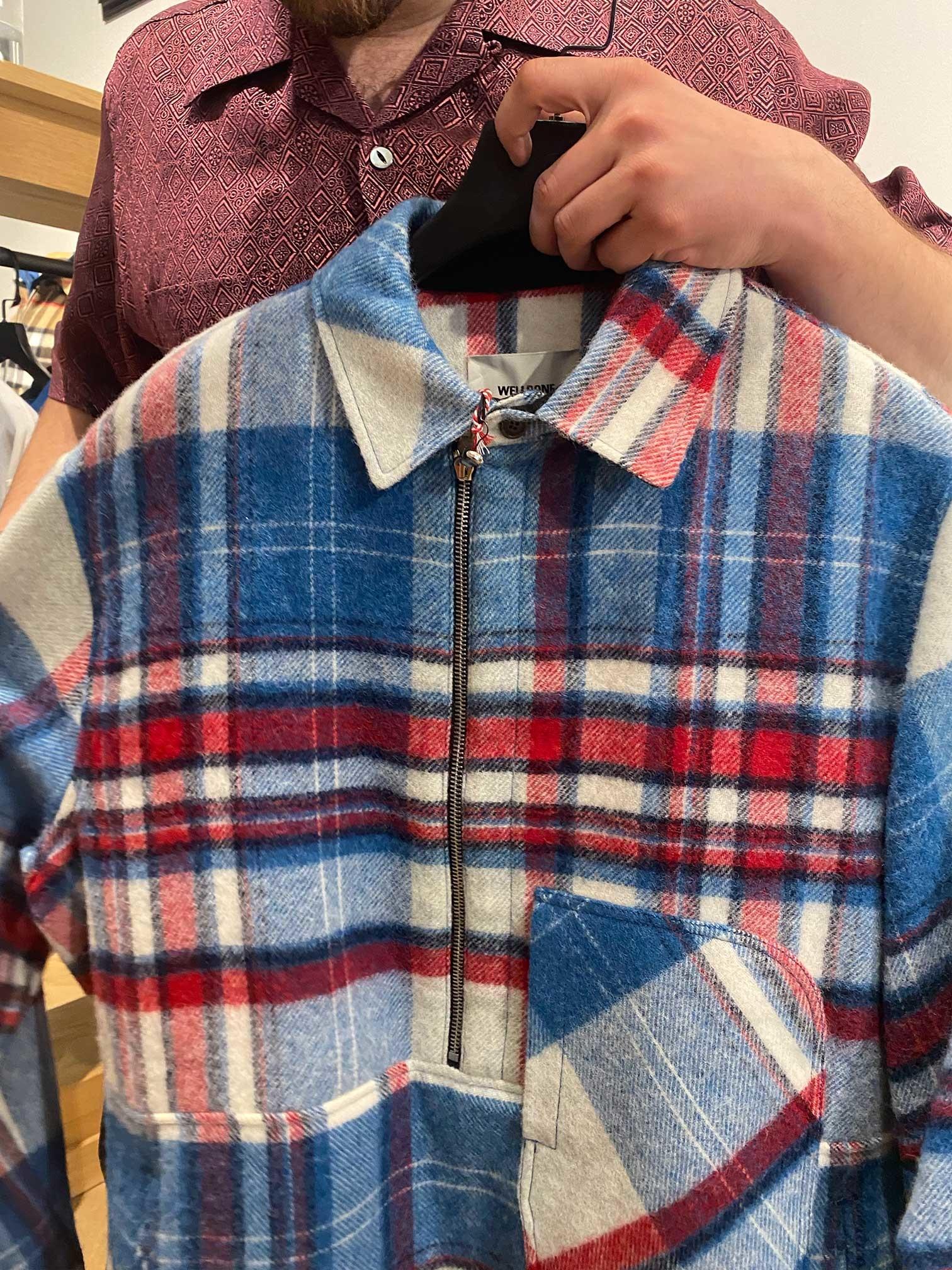 Sacha holds a WE11DONE anorak wool shirt