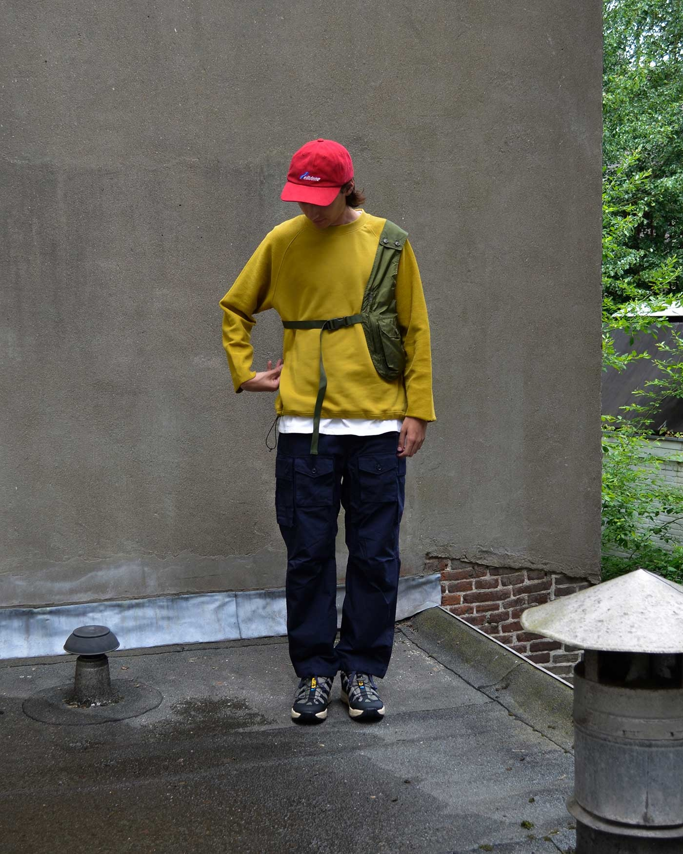 Noe wears a red WE11DONE cap, mustard Uniform Bridge sweater, Salomon shoes and both an Olive Engineered Garments shoulder bag and navy pants