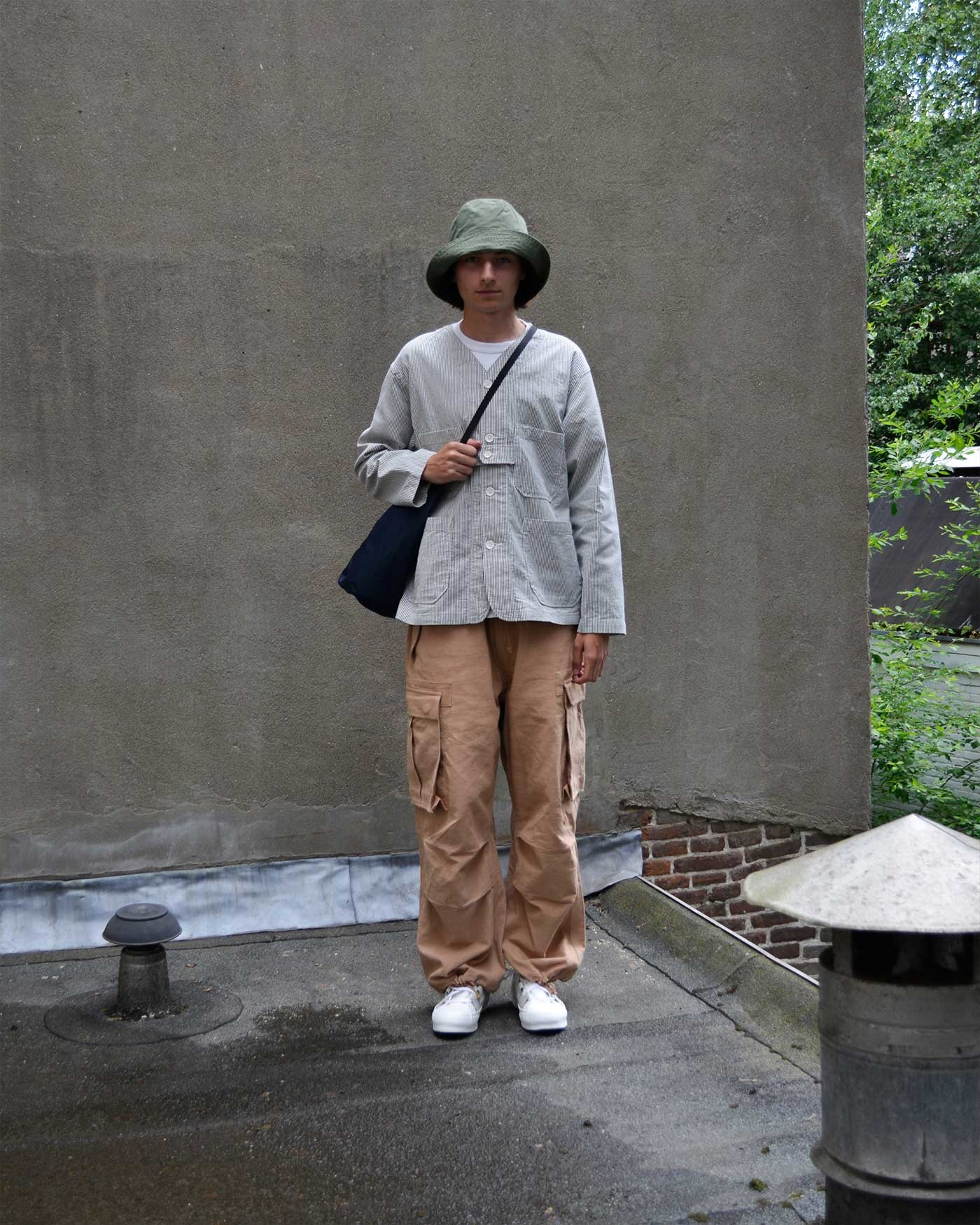 Noe wears a striped Engineered garments shirt jacket, olive bucket hat, Story MFG peace pants and Needles Ghillie sneakers