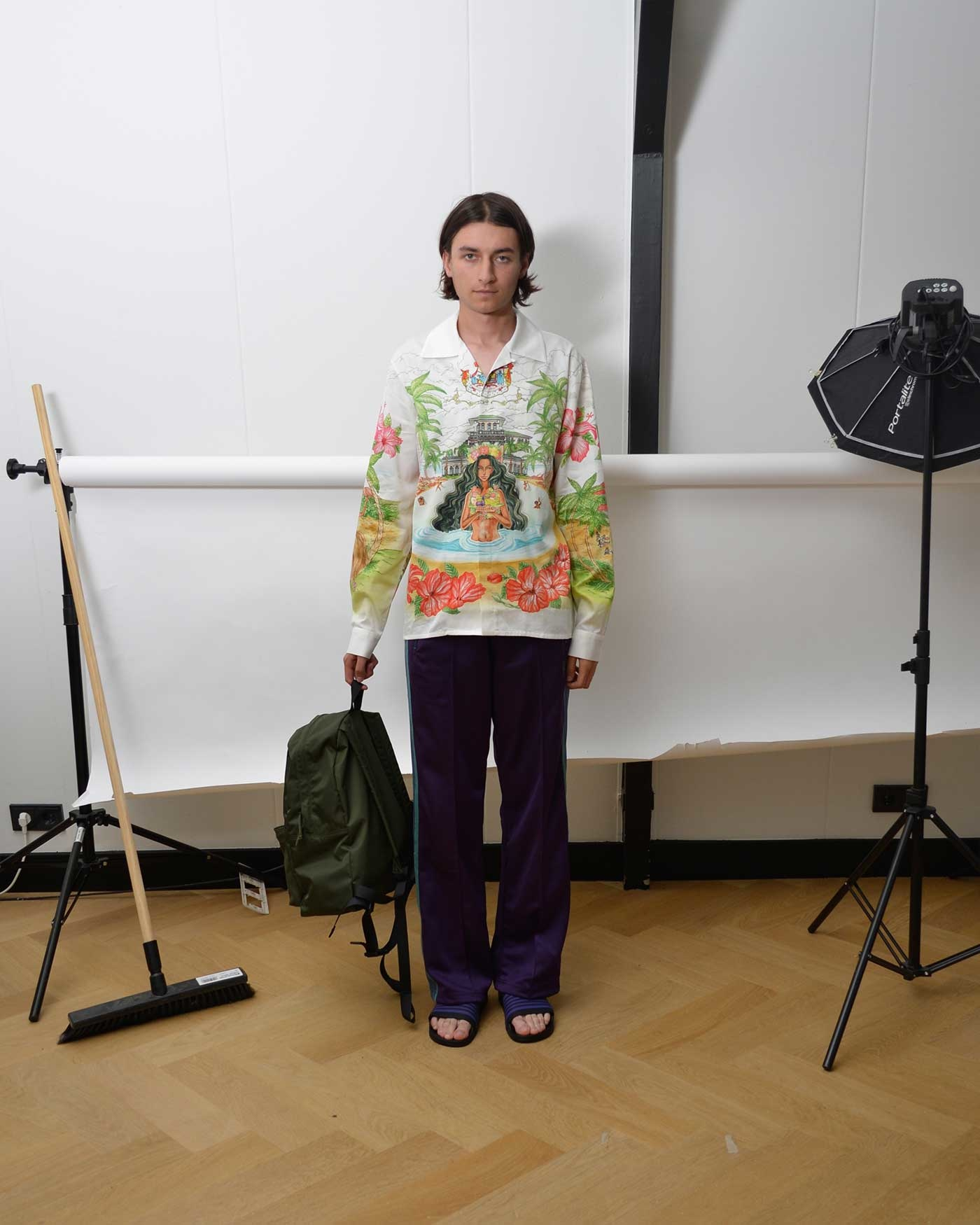 Noe wearing a printed casablanca Paris shirt, purple Needles Track Pants and Shower slideds