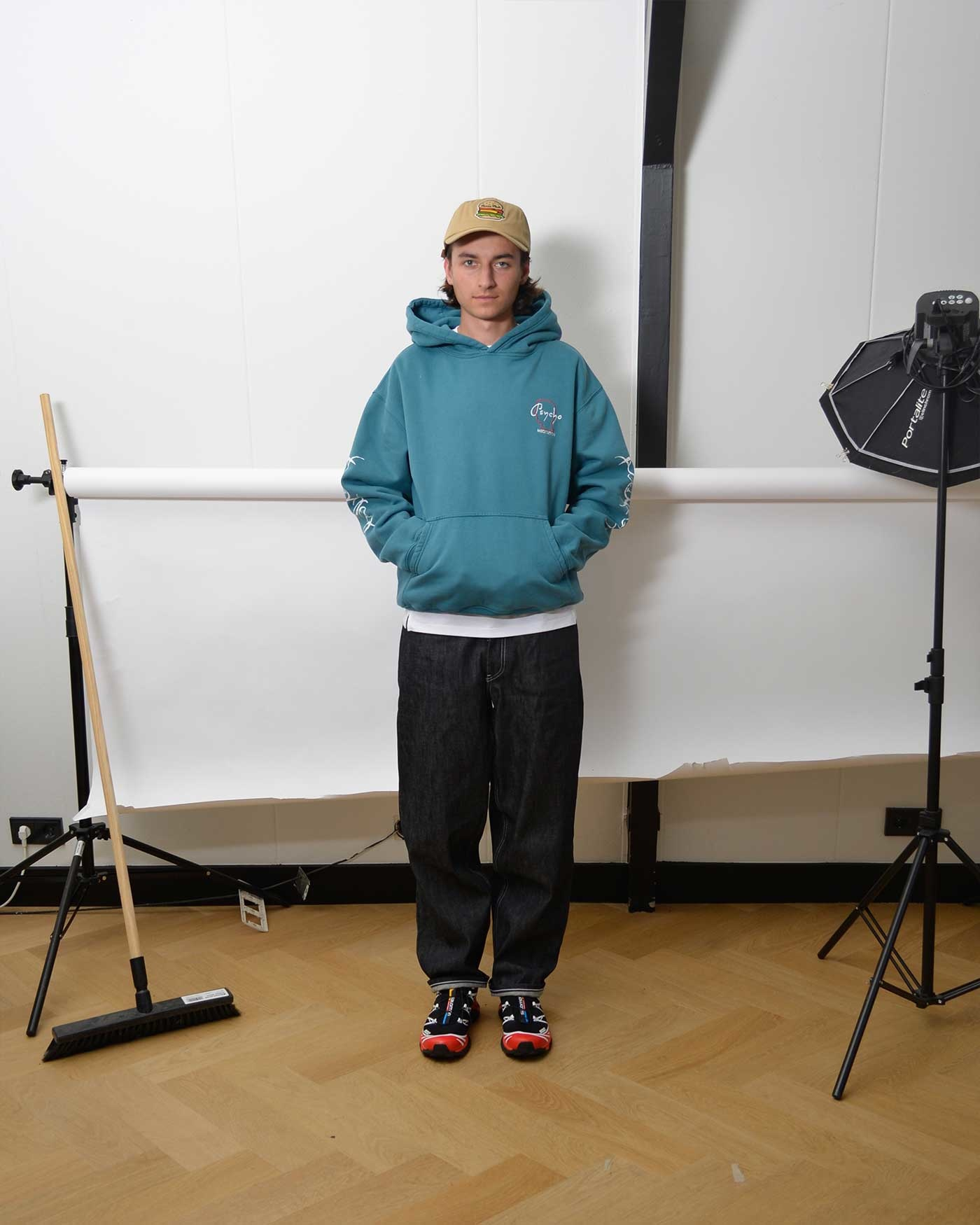 Noe wears a blue  graphic Brain Dead hoodie, beige Human Made cap, wide raw non denim jeans and black and red Salomon sneakers