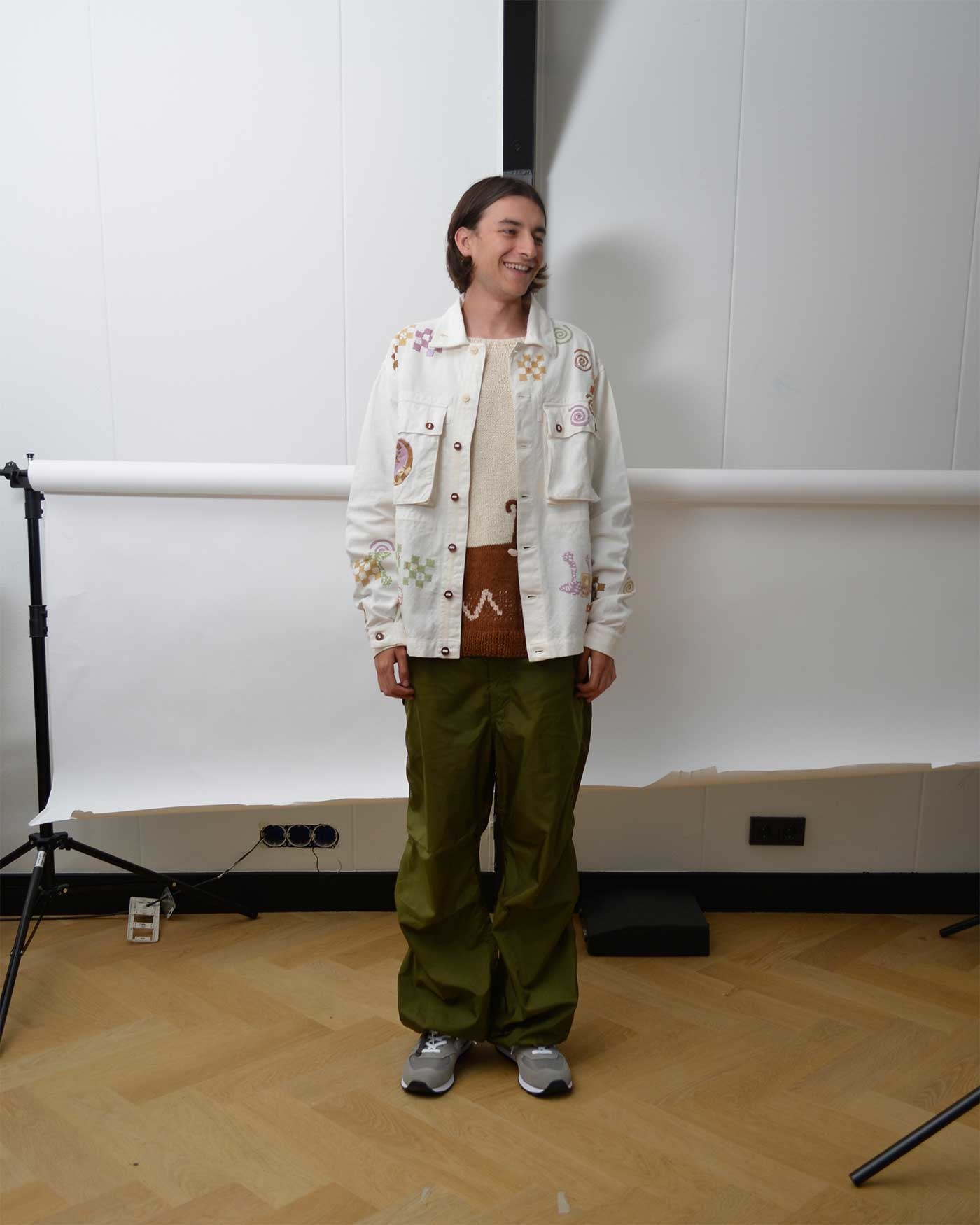Noe Wears an embroidered Story MFG jacket, knitted Story MFG sweater, olive Engineered Garments Pants and a pair of New Balance shoes