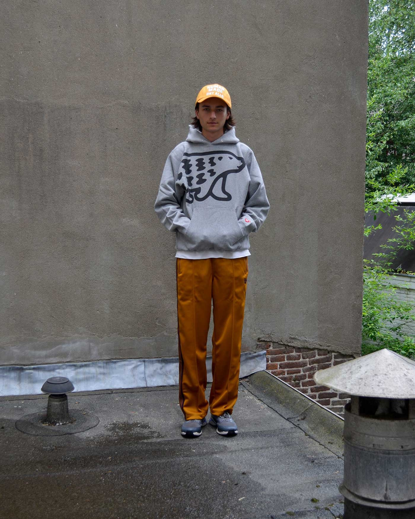 noe wears a grey printed Human Made hoodie, Yellow Human Made Cap, Gold Needles Track Pants and Salomon shoes