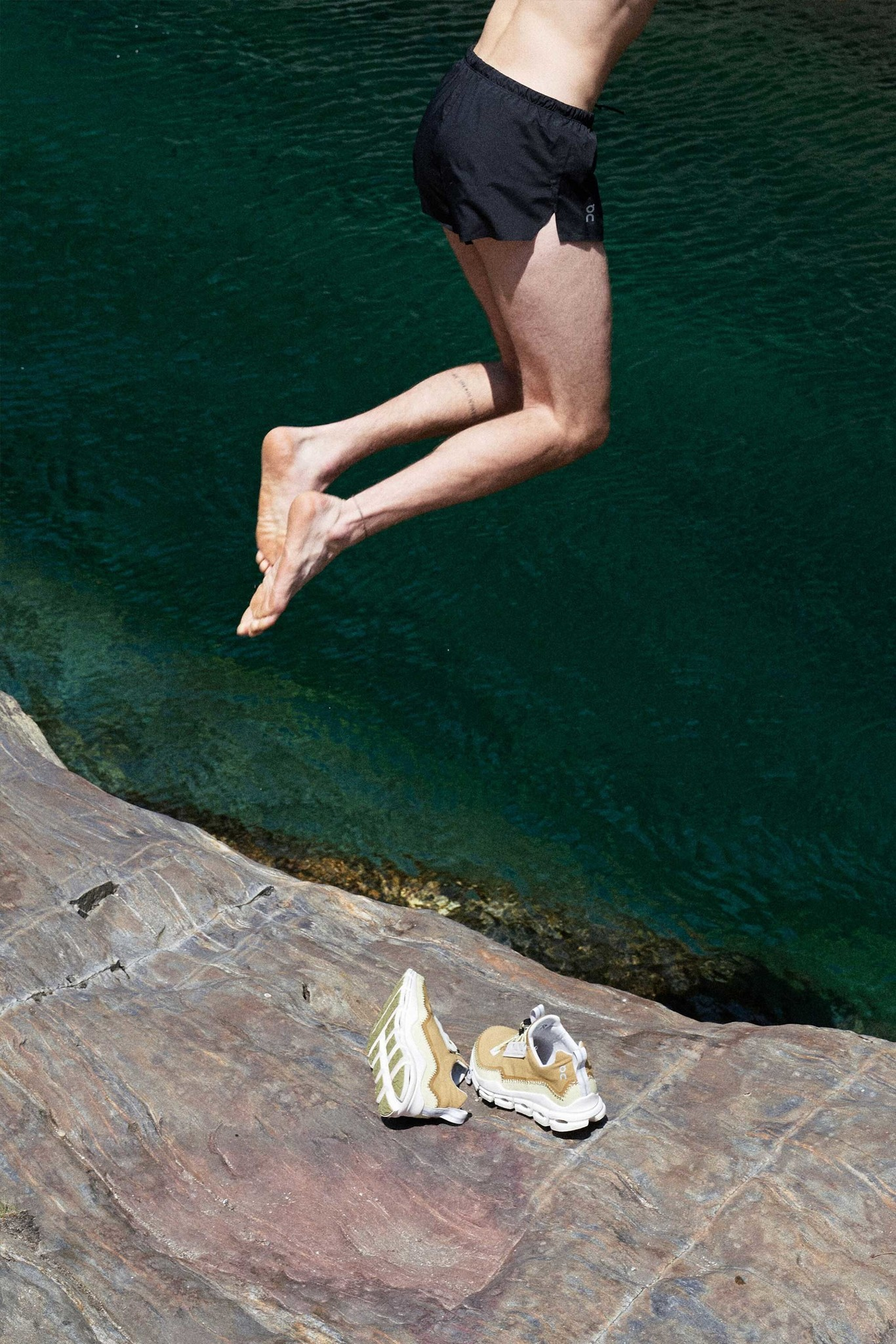 Model jumps off a cliff next to a pair of running shoes