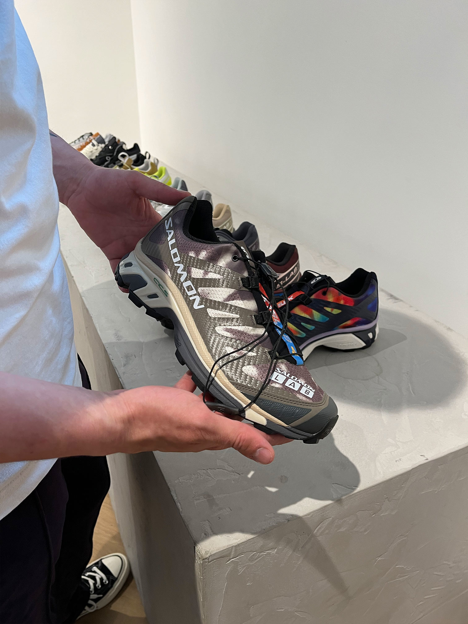 Rico holds up a pair of Salomon shoes