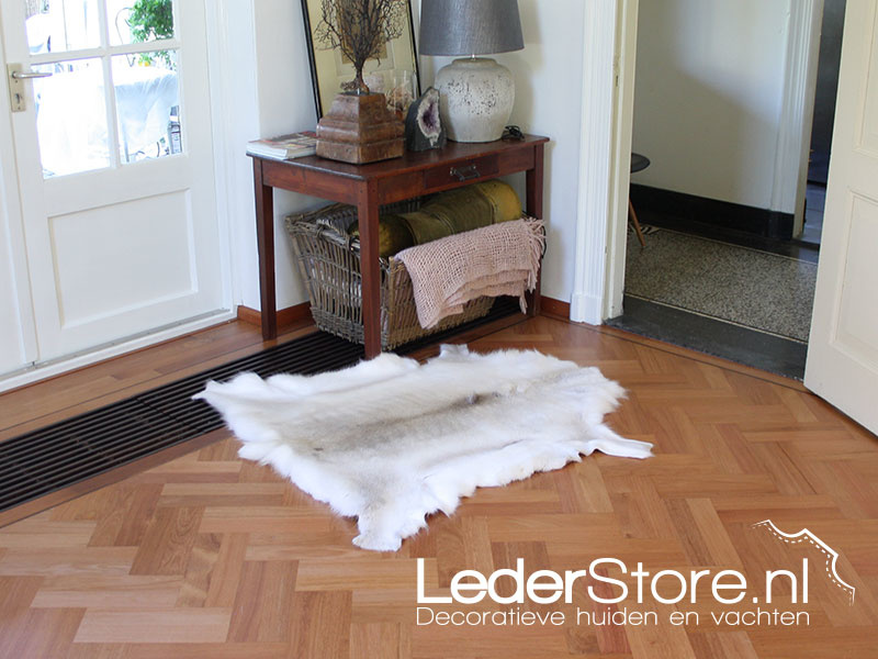 Witte rendierhuid op vloer