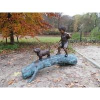 Beeld brons jongen met hond op boom