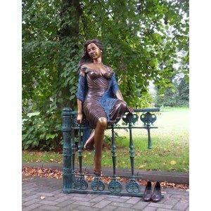 Eliassen Image bronze woman sitting on fence big