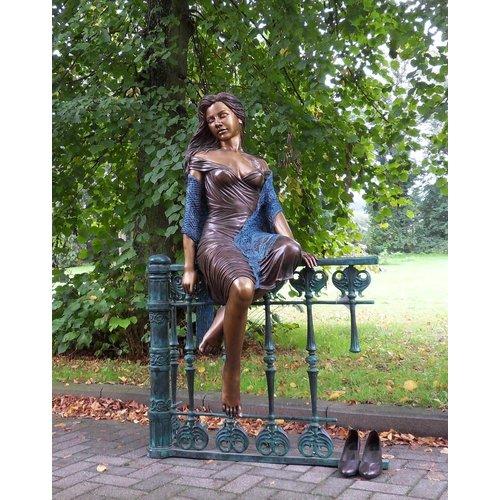 Eliassen Bildbronzefrau, die auf dem Zaun groß sitzt