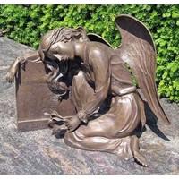 Grave statue angel against gravestone bronze