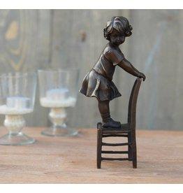 Eliassen Bildbronzemädchen, das auf Stuhl steht