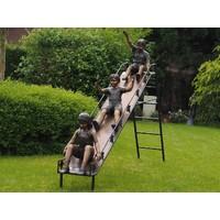Kinder auf einer Bronzerutsche