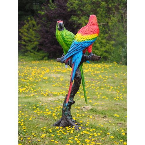 Bronzen papagaaien op boomstam