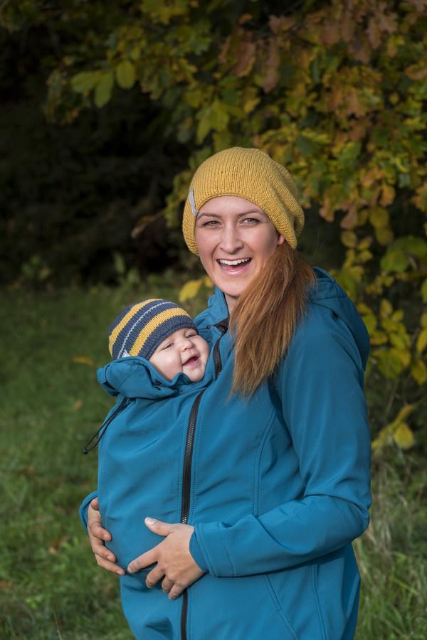 Vrouw met baby in blauwe softshell draagjas