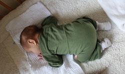 Baby in kikkerhouding op boxkleed