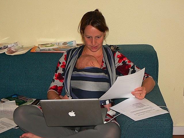 Vrouw met baby in draagdoek en laptop op schoot