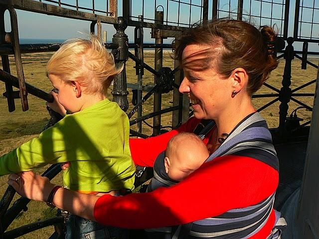 Vrouw met baby in draagdoek en kind op speeltoestel
